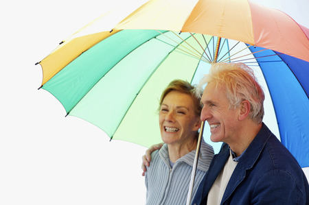 A couple chatting happily under a colorful umbrella