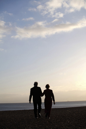 A couple walking hand-in-hand on the beach in the evening photo
