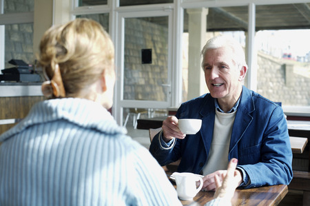 A man lifting a cup of coffee while talking to his wife photo