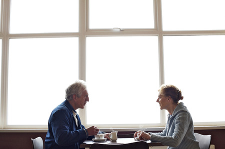 A mature couple relaxing and having coffee in a cafe photo