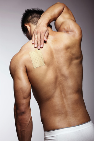 men body: Man putting pain relief patch on his back Stock Photo