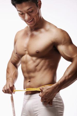 Man measuring his waist Banco de Imagens