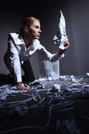 Businesswoman looking at opened crumpled paper photo