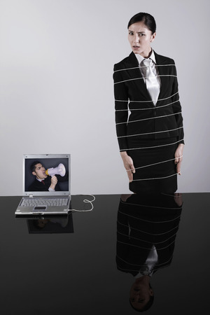 tiedup: Businesswoman tied up with rope connected to laptop Stock Photo