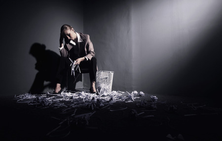 Businesswoman sitting on chair with hand on head and another holding shredded papers photo