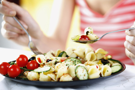 Woman enjoying a plate of fruit and vegetable pasta salad served with feta cheese and olives on the side photo