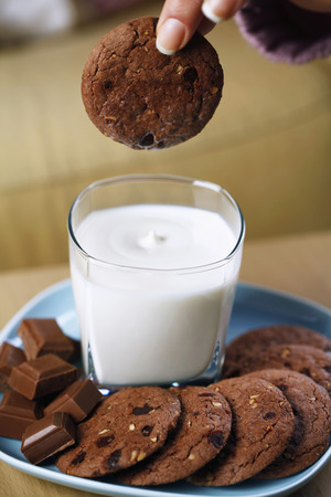 Woman dipping cookie into a glass of milk photo