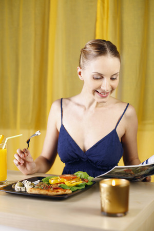 Woman reading magazine while enjoying her pizza and salad platter photo
