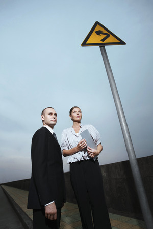 low blouse: Businessman and businesswoman standing on pavement beside a road sign Stock Photo