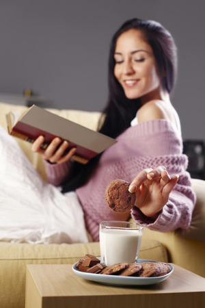 Woman dipping cookie into a glass of milk while reading book on the couch photo