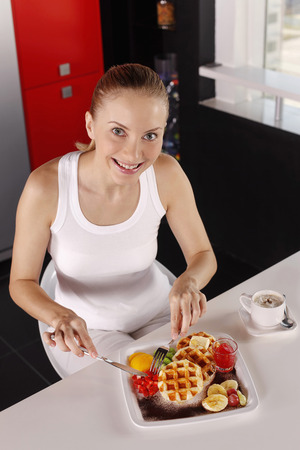 Woman enjoying a plate of lightly buttered waffle stacks with diced fresh strawberries and jam photo