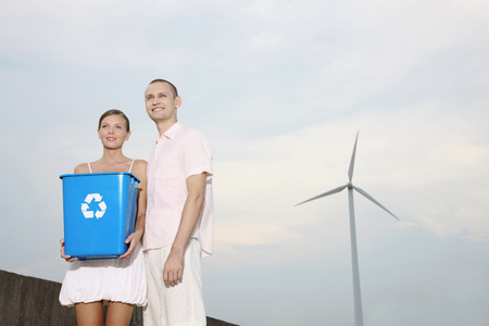 Woman holding recycling bin with man standing beside her photo