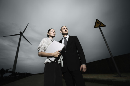low blouse: Businessman and businesswoman standing on the road, looking away