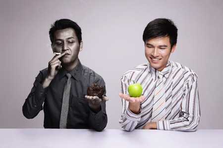 Businessman smoking while holding rotten apple, another businessman holding a fresh green apple photo
