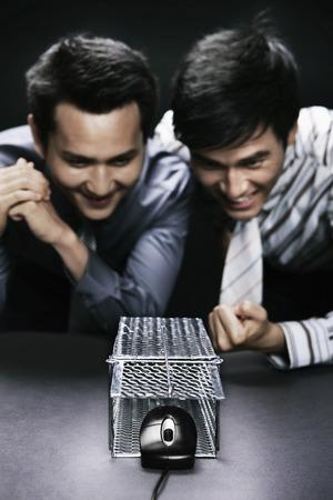piege souris: Les hommes d'affaires en regardant dans l'excitation que la souris d'ordinateur de sortir d'un pi�ge � souris