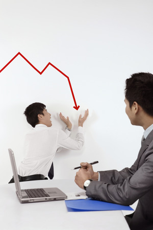 Businessman trying to prevent line graph from going down photo