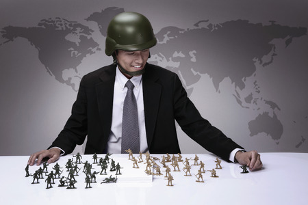 Businessman playing with toy soldiers photo