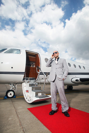 Man with headset standing by private jet photo