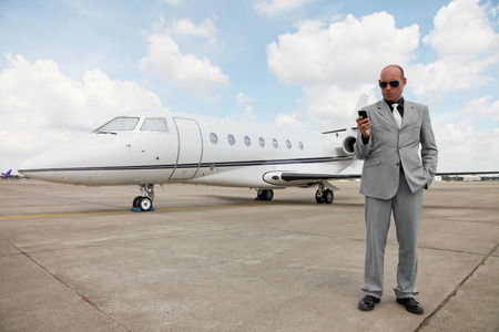 Man text messaging on the phone with private jet in the background photo