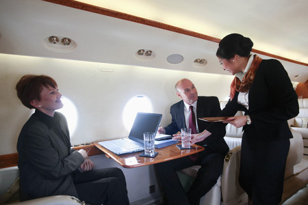 Flight attendant serving businessman and businesswoman in private jet