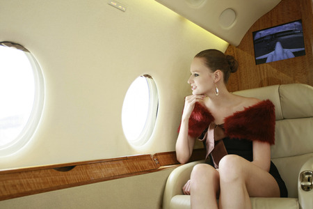 Woman looking out of the window in a private jet photo
