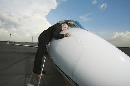 Businessman lying on front of private jet photo