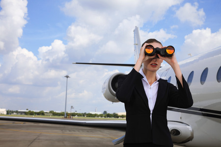 Businesswoman looking through binoculars with private jet in the background photo
