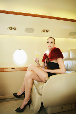 Woman sitting in private jet holding a glass of champagne Stock Photo