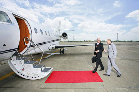 Businessmen walking towards private jet Stock Photo