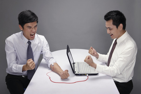 jubilating: Businessman transferring blood from his hand to laptop through IV drip tube, another businessman jubilating