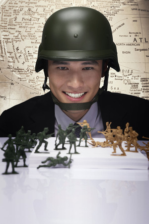 Businessman looking at toy soldiers photo