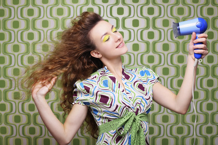 Woman blow-drying her hair with hair dryer photo