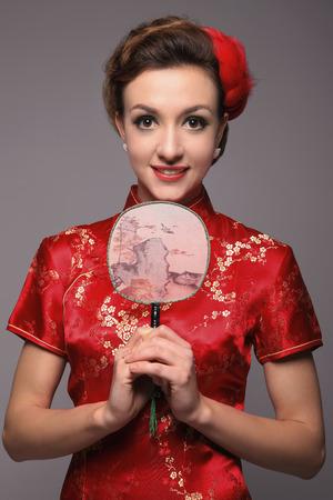 qipao: Woman in cheongsam holding Chinese oriental fan