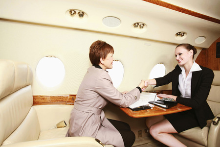 Businesswomen shaking hands in private jet photo