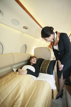 Flight attendant checking on resting businesswoman photo