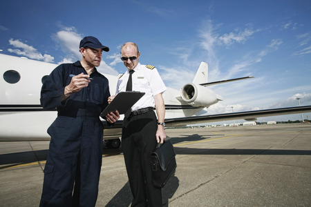 Plane engineer and pilot looking at document on clipboard photo