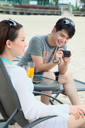 Man taking a picture of woman relaxing at lounge chair photo