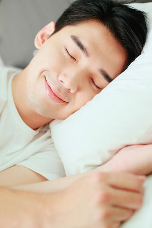 Man sleeping on bed Stock Photo - 26386080