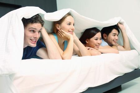edred�n: Hombres y mujeres que yacen en la cama cubierta por consuelo