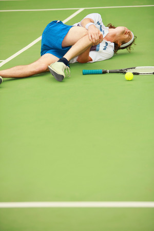 Man with knee injury while playing tennis