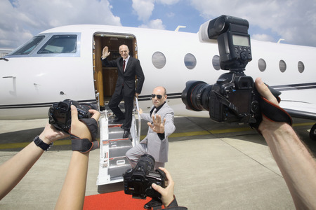 Businessman descending from private jet with his bodyguard, paparazzi taking photographs Stock Photo