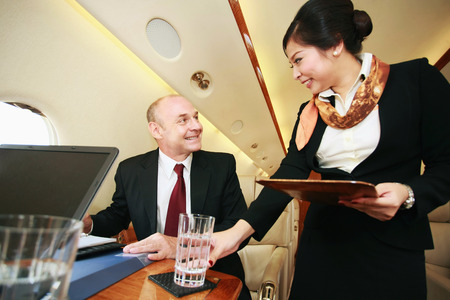Flight attendant serving businessman a glass of water
