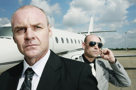Businessman with his bodyguard and a private jet in the background photo