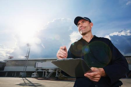 Mechanic examining private jet at plane runway photo