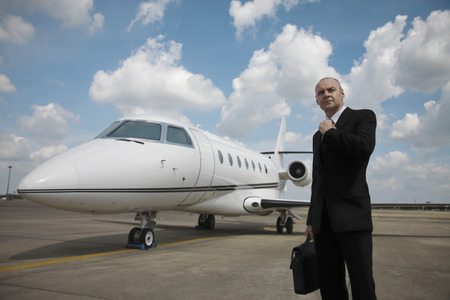 Businessman adjusting his tie on runway with private jet in the background photo