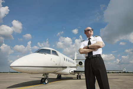 Pilot standing at runway with private jet in the background photo