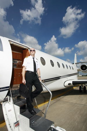 exiting: Pilot exiting private jet holding a briefcase Stock Photo