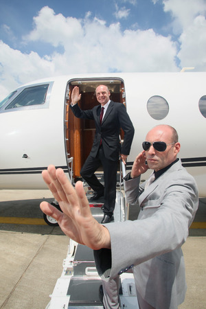 Businessman descending from private jet with his bodyguard