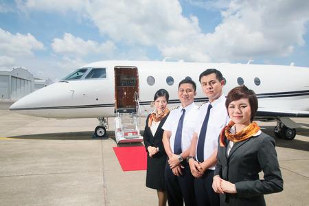 Pilotów i stewardes stojące przez prywatnego odrzutowca Zdjęcie Seryjne