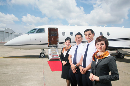 Pilots and flight attendants standing by private jet